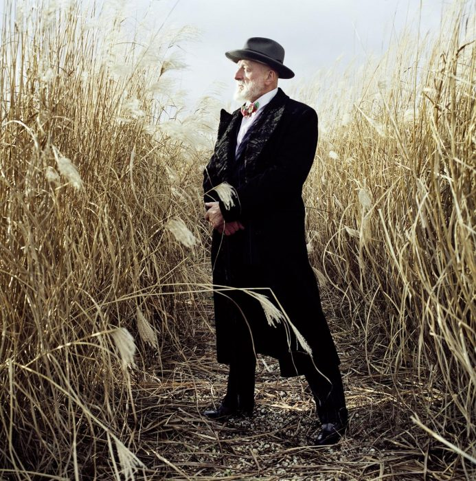 Formally dressed bearded man standing in a cornfield