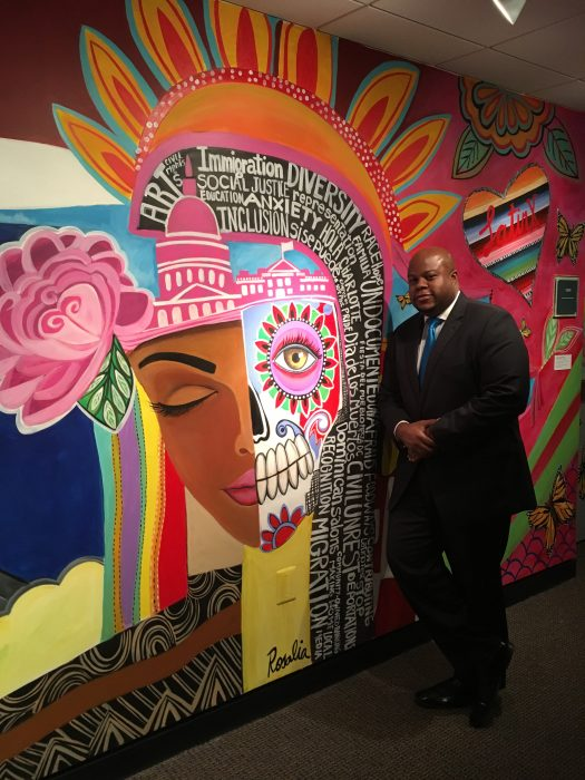 Man in suit leans against colorful mural wall