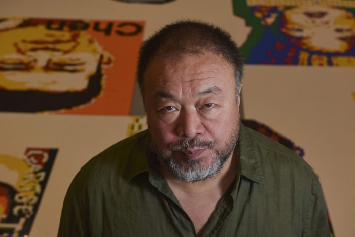 Wewei looks into camera, exhibition in background