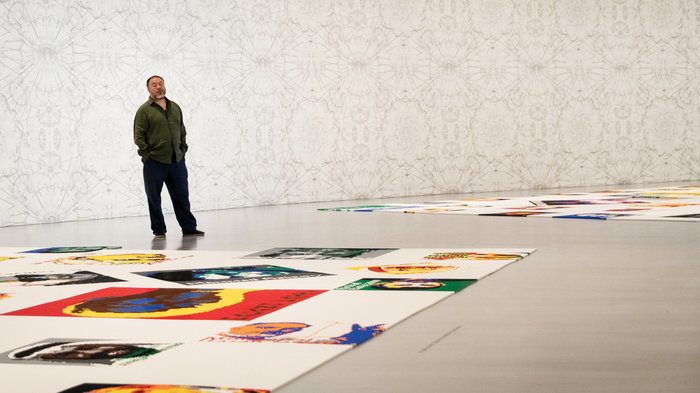 Ai Weiwei in gallery with portraits on floor