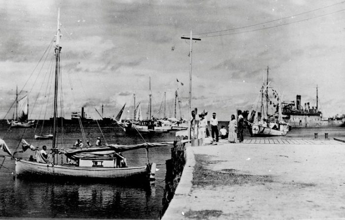 History photo of pier with boats, people in distance