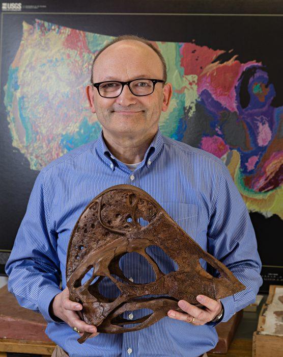 Hans Sues holding dinosaur skull