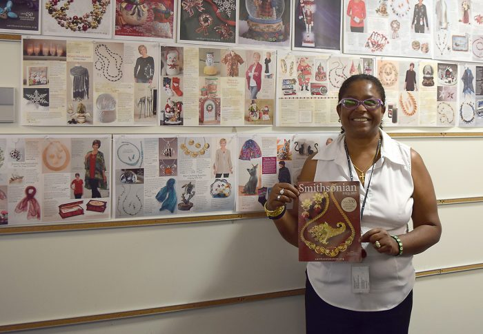 Marie Dieng holds catalog in front of wall display showing pages