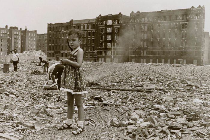 Photo of little girl in rubble-strewn vacant lot