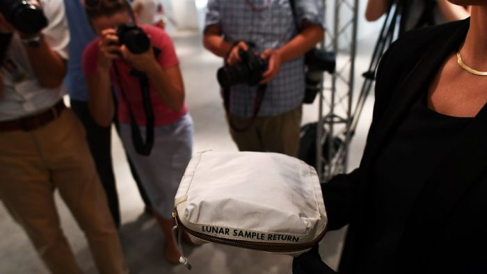 Photographers take pictures of bag marked Lunar Sample Return