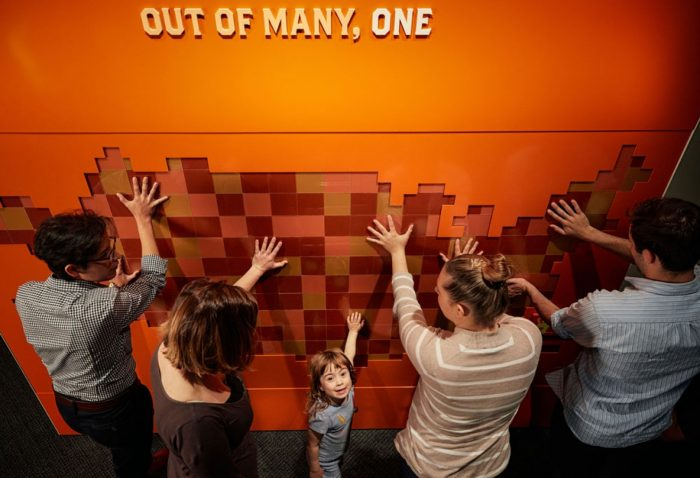 Visitors placing their hands on map, child looking up at camera