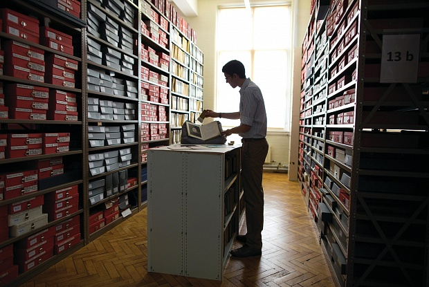Man working qwith documents amid shelves of collection boxes