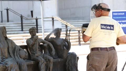 Man wearing welding helmet works on sculptures
