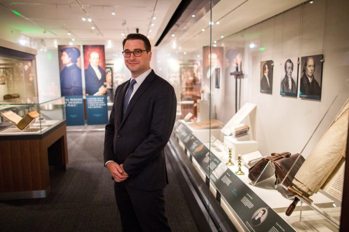 Curator standing among display cases