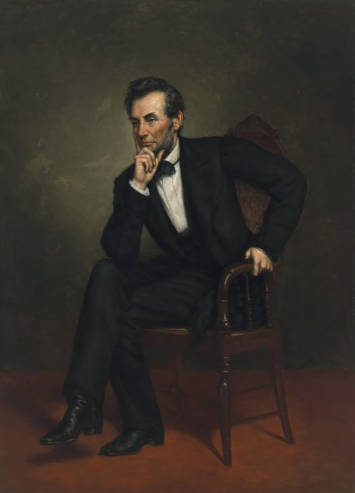 portrait of Lincoln seated on chair with chin in hand