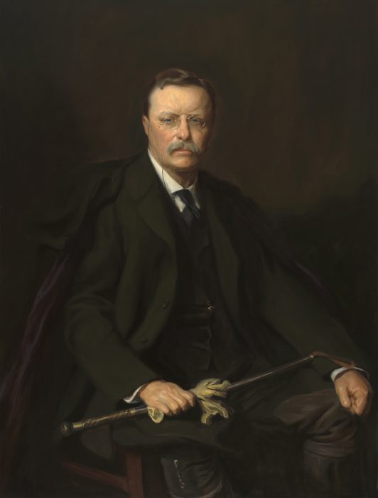 Portrait of Theodore Roosevelt holding riding crop and gloves