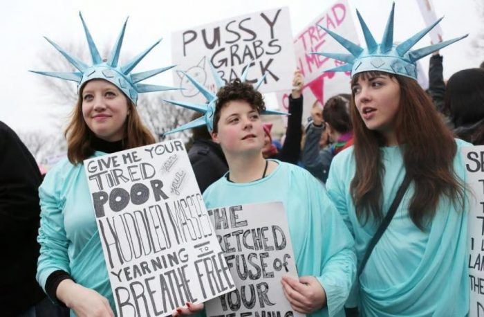 Women holding signs and wearing Liberty costumes