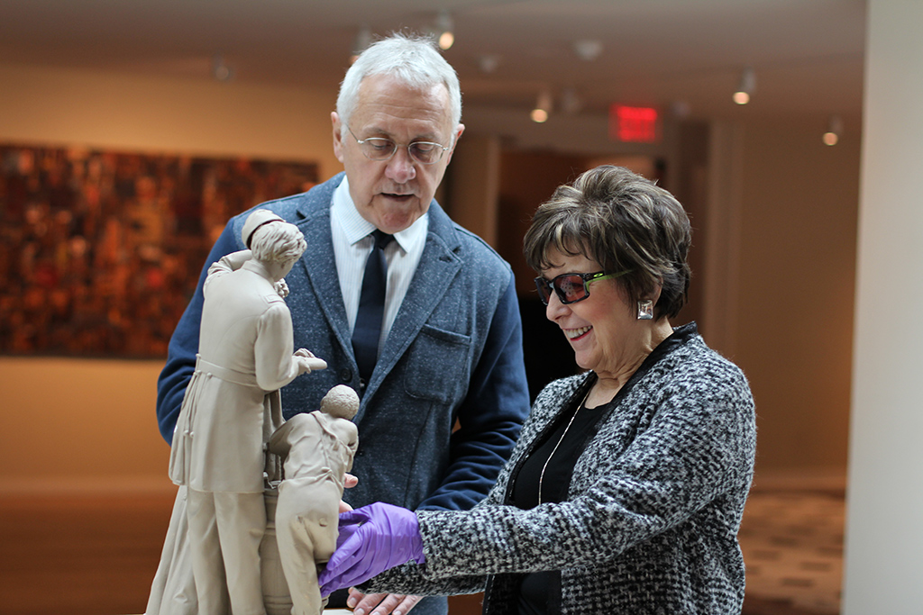 Woman wearing curator's gloves touches statue while docent looks on