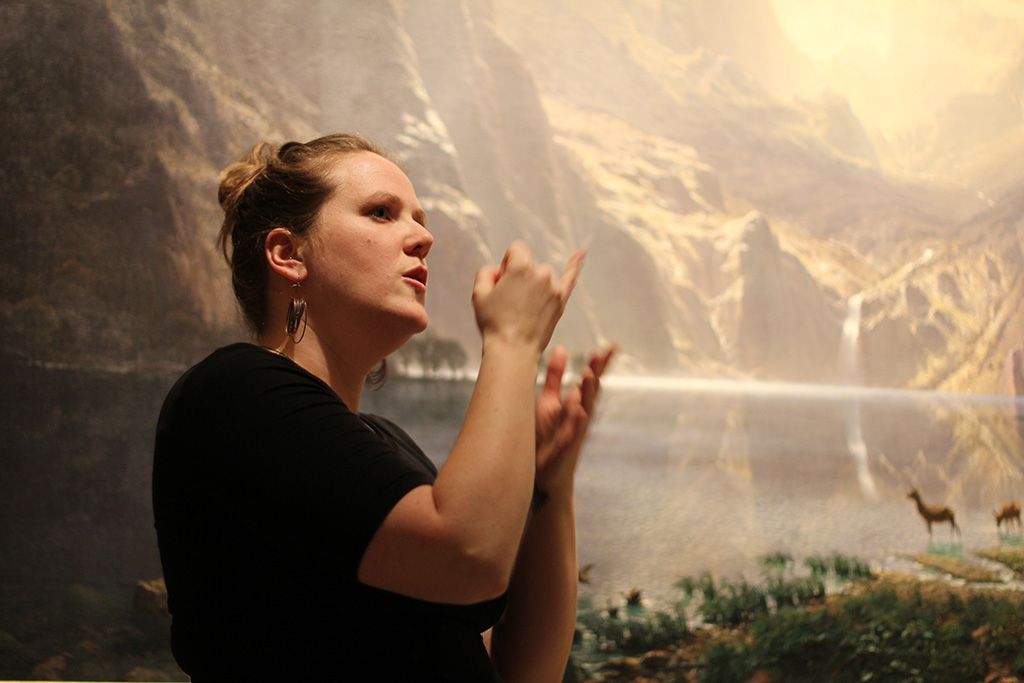 Woman discusses large landscape painting in ASL