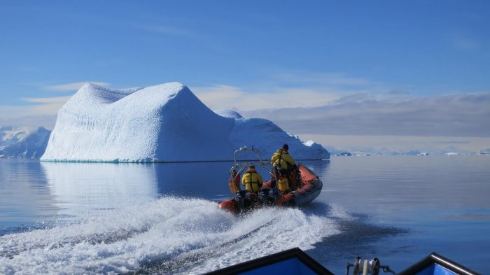 researchers in small boat with ice floe in background