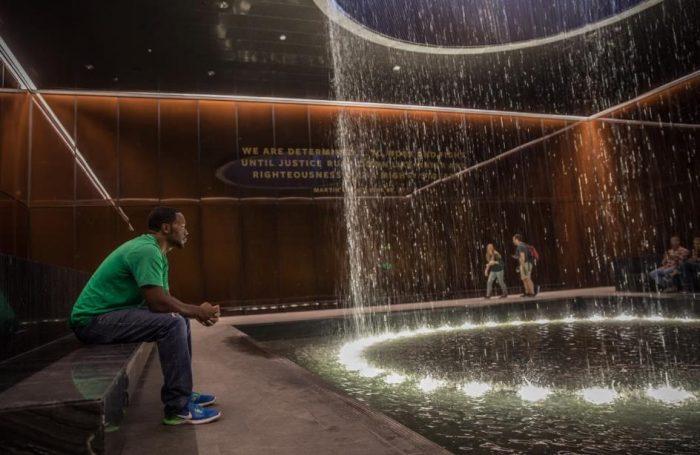 Man in green shirt gazes at fountain
