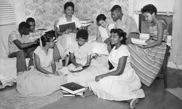 Group of teenagers posed as if studying