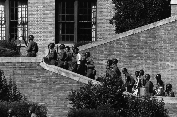 Black teenagers surrounded by armed soldiers climb stairs into high school