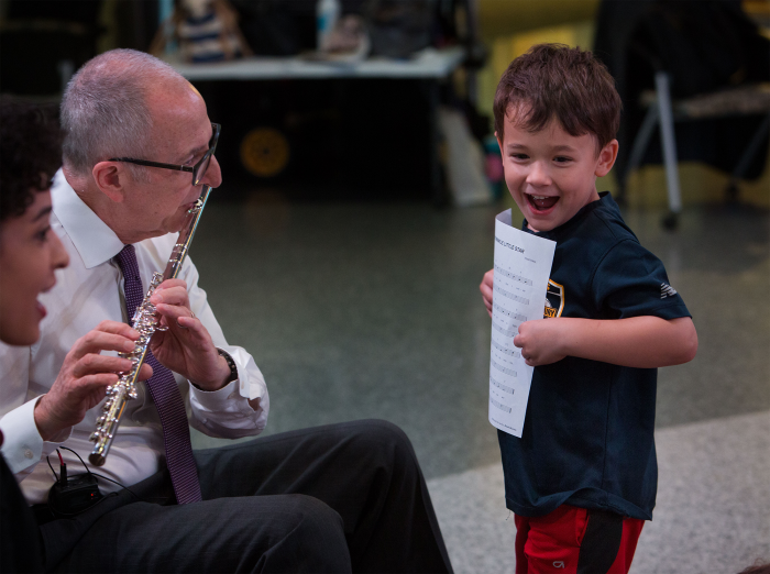 Laughing child holds music as Skorton plays the flute