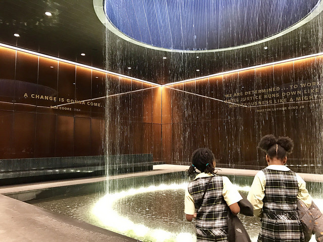 Two girls in school uniforms stand in front of waterfall fountain