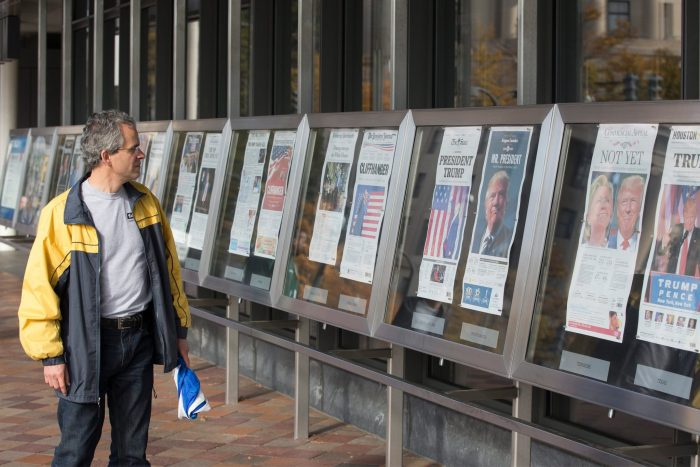 Man looks at display of newspapers