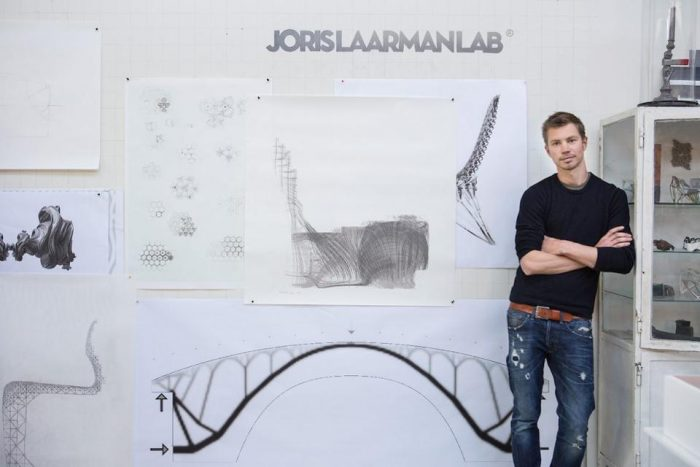 Artist leans against shelf with drawing on wall behind him