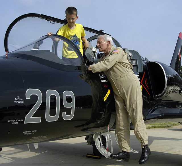 Dailey in flight suit demonstrates controls for child in cockpit