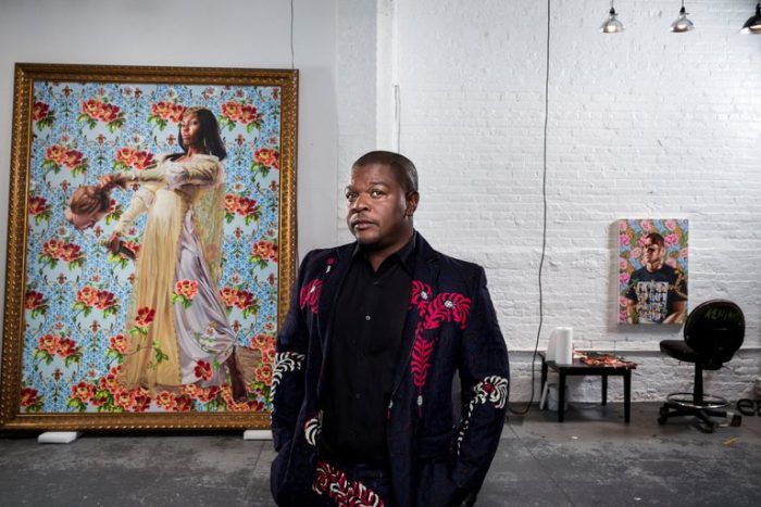 Artists stands in front of one of his portraits