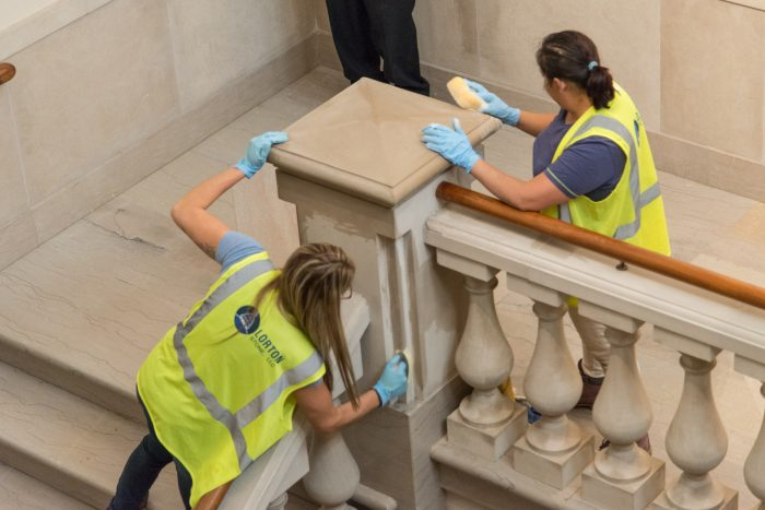 cleaning crew works on marble staircase