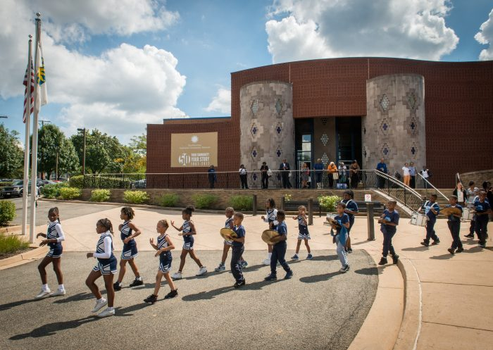 drum line of young kids marches in front of museum