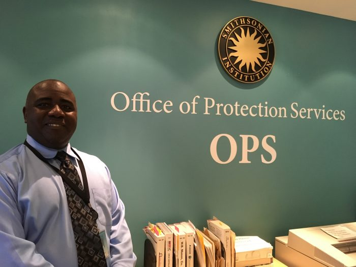 McKinney standing next to Office sign on wall