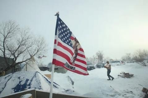 Snow-covered camp with US flag in foreground