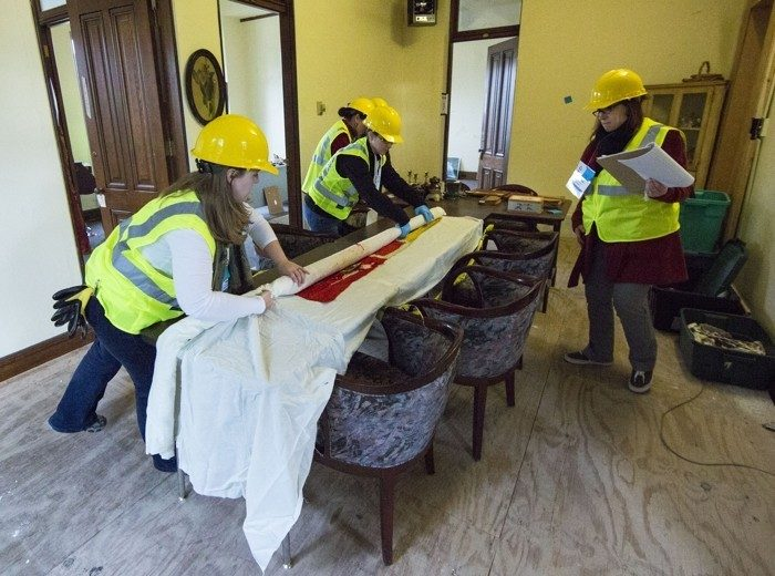 workers in hard hats wrap artifacts