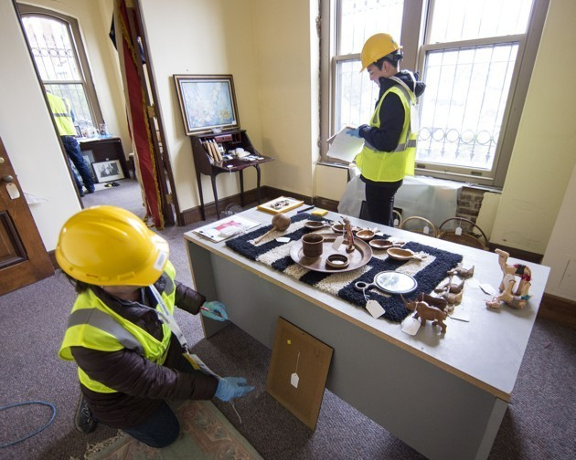 Workers in hard hats wrap ceramics