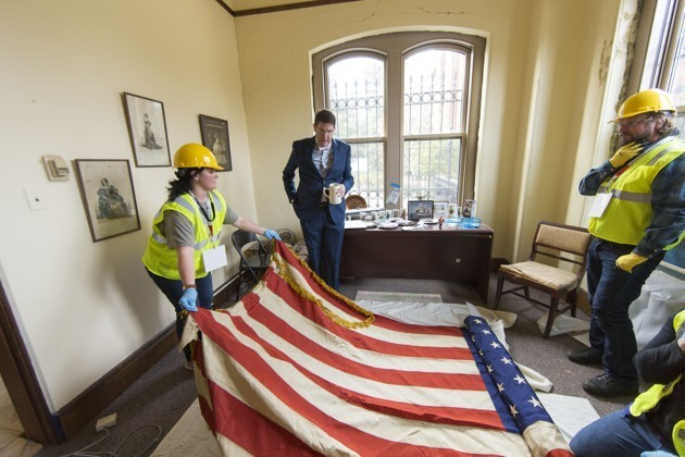 Workers in hard hats roll up American flag