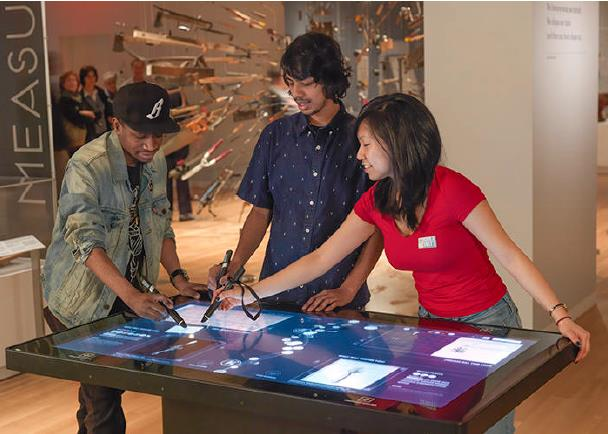 Visitors use digital pen on large touch screen