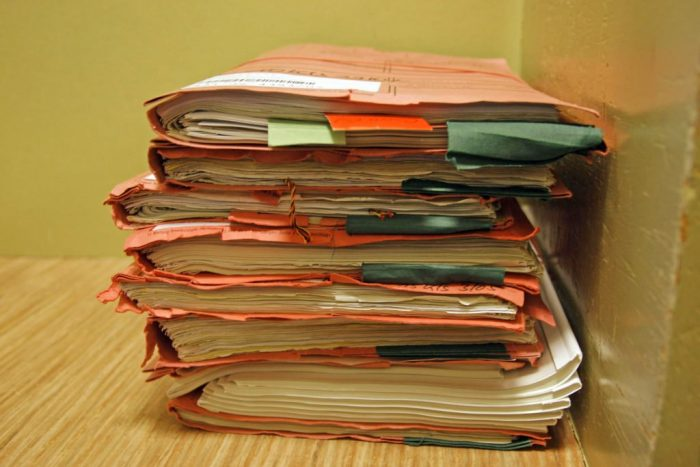 Stack of tattered file folders full of documents