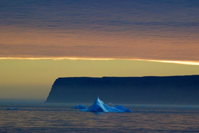 photo of iceberg in foreground, with Saunders Island in background