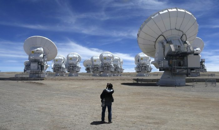 Telescopes on high desert plateau, photographer in foreground