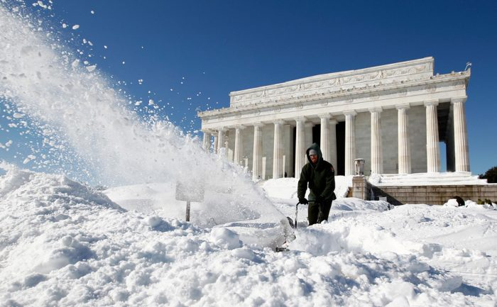 Worker using snowblower in front of federal building