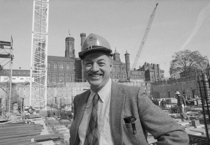 Adams on construction site, Castle in background