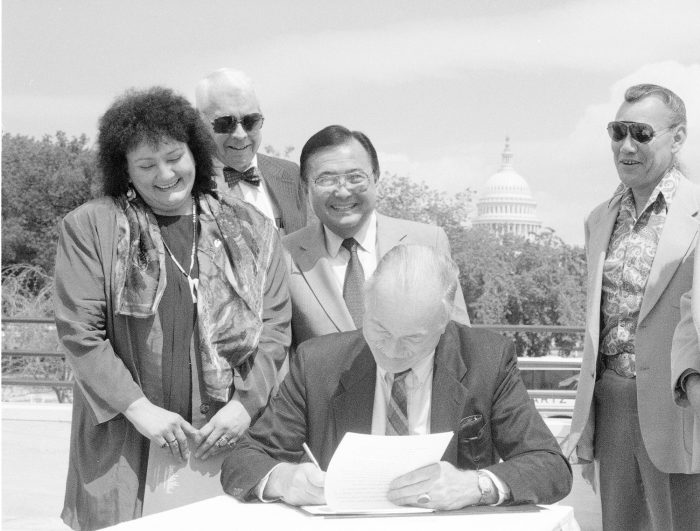 Adams signing documents, Capitol in background