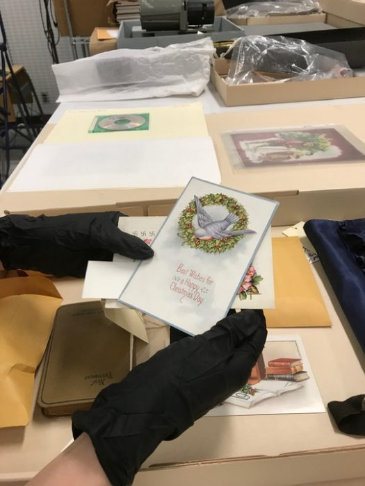 Curator wearing gloves displays holiday card