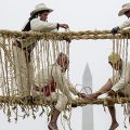 Cropped photo of men building rope bridge
