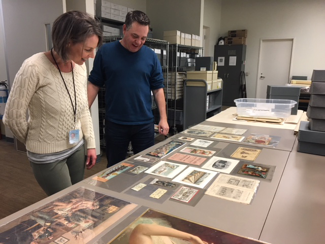McCulla and Hursey examining old advertising laid out on table
