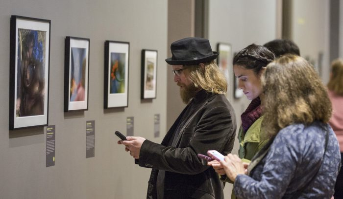 Gallery visitors check their phones