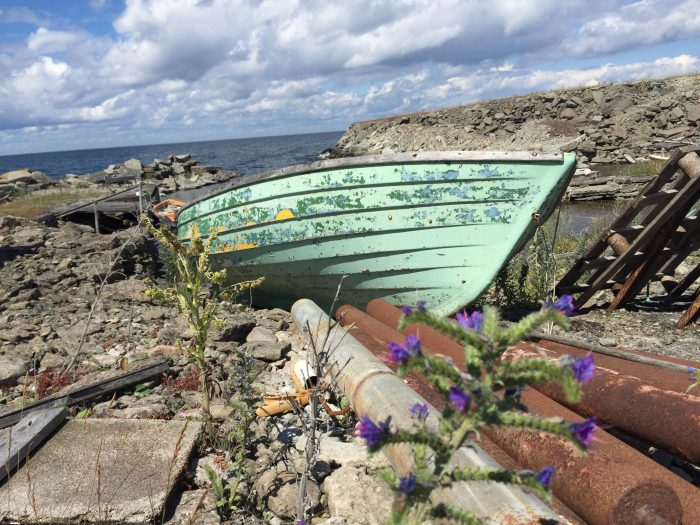 A weathered boat rests on the shore of Öland Island, Sweden.