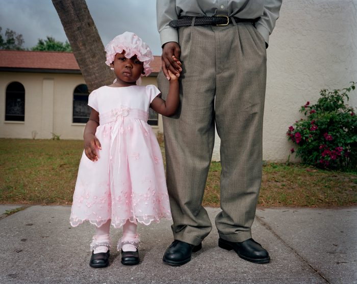 A young girl and her cousin wait after Creole Mass at a Catholic Church in Immokalee, Florida.