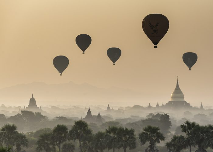 A view of temples and the surrounding landscape at dawn in the Bagan area of Myanmar.