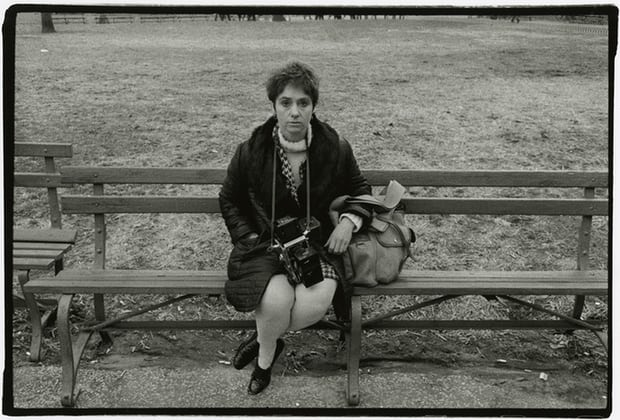 Black and white photo of Arbus sitting on bench